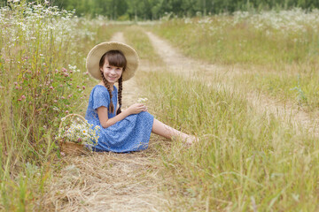 Photo sur Toile Doux monstres Cute girl and basket of flowers on the field