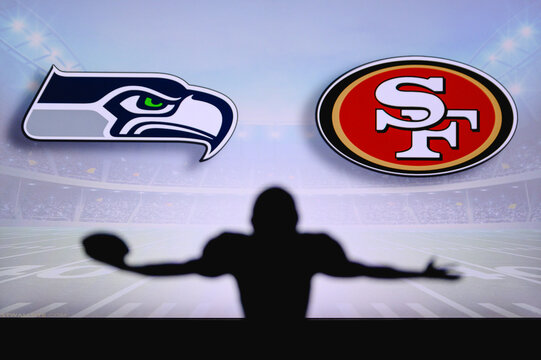 Seattle Seahawks vs. San Francisco 49ers. NFL Game. American Football League match. Silhouette of professional player celebrate touch down. Screen in background.