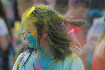 Woman covered in coloured powder reacts during the ColorFest at the amusement park 'Dreamland' in Minsk