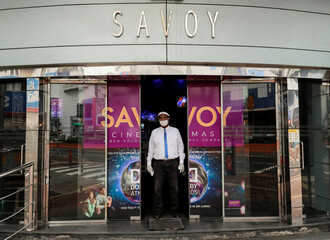 A staff member wearing a protective mask waits outside the Savoy cinema, amid concerns about the spread of the coronavirus disease (COVID-19), in Colombo