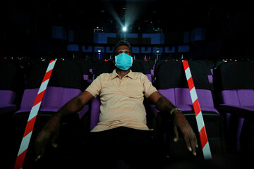 A cinema patron wearing a protective mask watches a movie at Savoy cinema, amid concerns about the spread of the coronavirus disease (COVID-19), in Colombo
