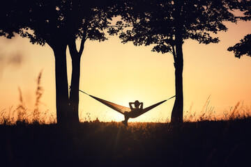 People on vacation. A girl's silhouette in a hammock between trees. A hammock in the background of the sunset. Rest and relaxation in nature.