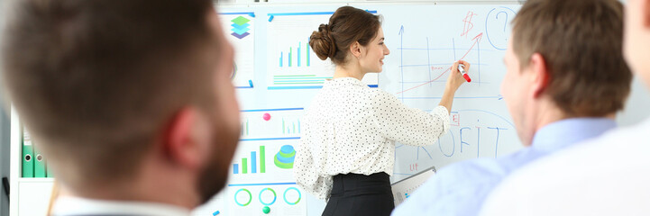 Smiling beautiful woman in office telling something important while showing information on white board