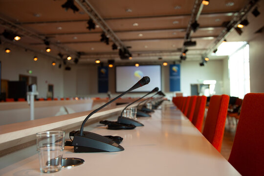 A large meeting venue with microphones and a big display in the background