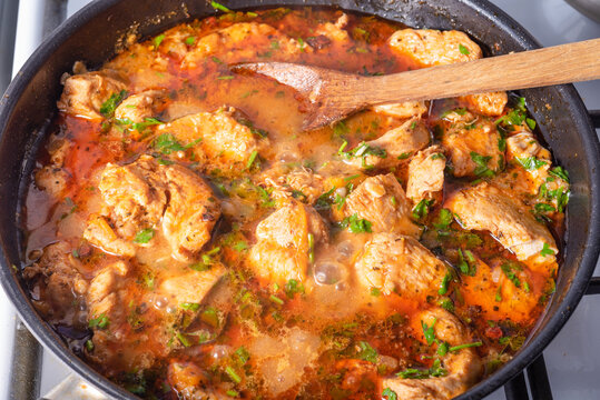 Cooking chicken with spicy sauce, Italian cuisine - Arrabbiata garlic chicken with parsley is cooked in a pan, close-up