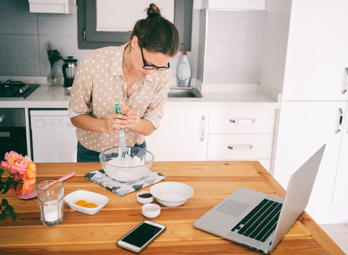 Beautiful young woman in glasses prepares dessert in the kitchen, whips whites and dough, cooking class online