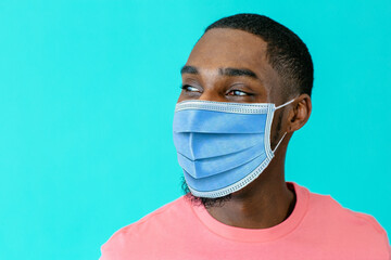 Portrait of a young african man wearing mask for coronavirus looking to side, against blue studio background