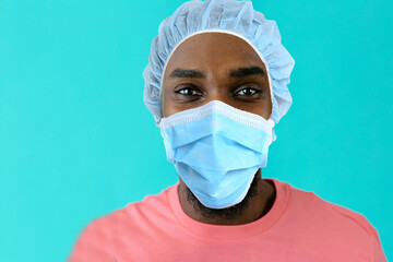 Portrait of a young african person wearing mask and hair cap for coronavirus protection looking at camera, against blue studio background