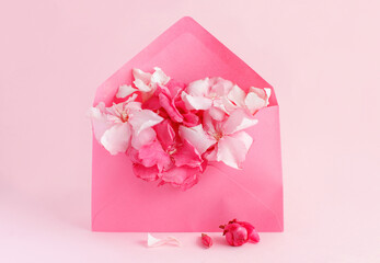 Pink envelope full of flowers  over a pink background