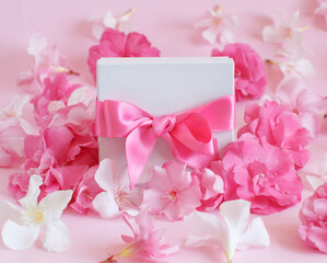 White gift box with a bow between pink flowers