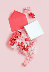 Red envelope and gift box full of flowers  over a pink background