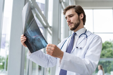 hospital doctor holding patient's x-ray film, radiologist studying x-ray results.
