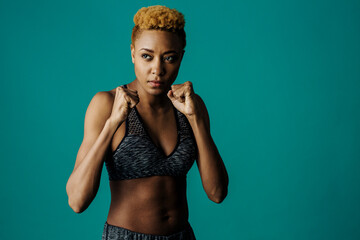 Portrait of a serious female athlete in sports bra and gym clothes with fists up ready to train, against studio background