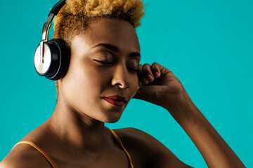 Close up portrait of a young  woman with headphones listening to music with eyes closed