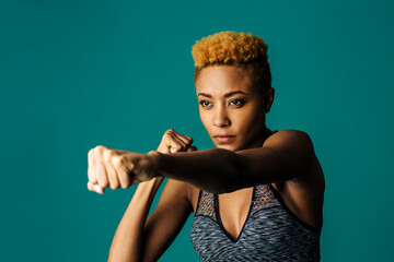 Portrait of a serious female athlete in sports bra and with fists up boxing against studio background