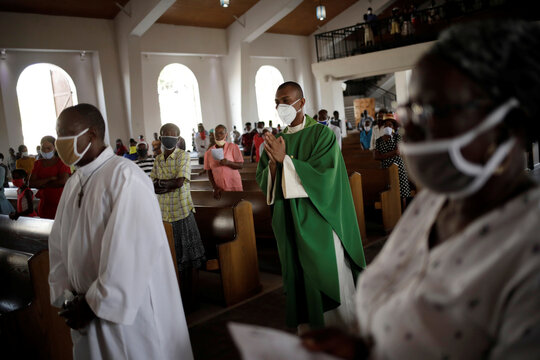 Priests, wearing face masks, walk as Catholic faithful attend to a mass on the first day of the reopening of temples and worship places, amid the coronavirus disease (COVID-19) outbreak, at the Cathedral of Port-au-Prince