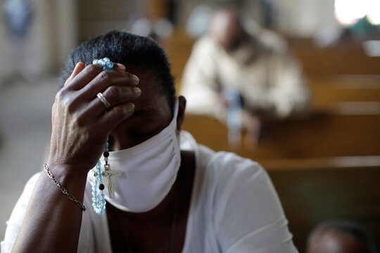 A Catholic faithful, wearing a face mask, prays during a mass on the first day of the reopening of temples and worship places, amid the coronavirus disease (COVID-19) outbreak, at the Cathedral of Port-au-Prince