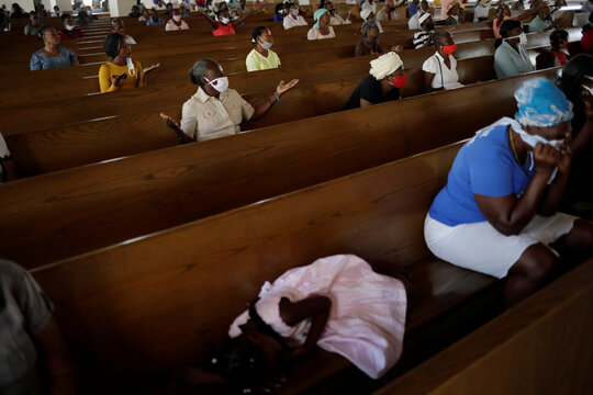 A girl sleeps on a bench as Catholic faithful pray during a mass on the first day of the reopening of temples and worship places, amid the coronavirus disease (COVID-19) outbreak, at the Cathedral of Port-au-Prince