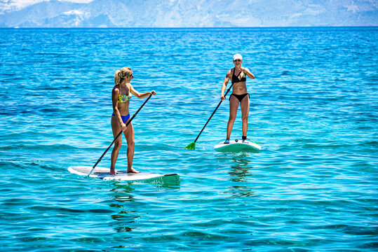Two women are paddling on a SUP on the crystal clear waters in the hot day. Healthy lifestyle concept.