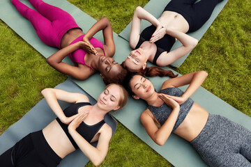 Peaceful young girls relaxing on mats during their yoga practice outdoors, overhead view