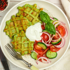 Delicious healthy green waffles with zucchini, spinach and Basil. It is served with a salad of fresh vegetables-tomatoes, cucumbers and red onions with olive oil and spices. Selective focus