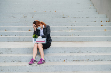 A woman with a box of personal belongings sits on the stairs outside and folded her hands in...