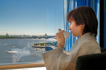 Woman drinks tea near large window in hotel. Woman looks at the landscape of  summer city with river. Portrait side view