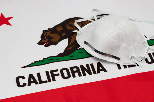 California state flag and N95 face mask. Concept of state and local government face covering mandate, order, requirement and social distancing during Covid-19 coronavirus pandemic