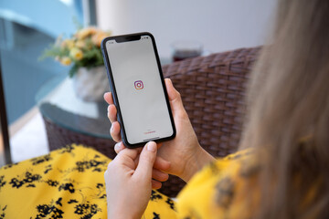 Woman hand holding iPhone 11 with social networking service Instagram