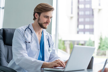 Young male doctor working on laptop computer, sitting in medical office.