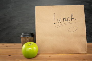 Eco brown paper lunch bag with smile on wooden table with apple and coffee cup as time for snack during education. Chalk board on background with copy space. Back to school concept. Space for text.