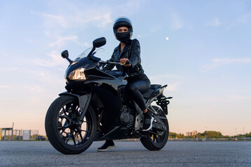 Attractive girl with long hair in black leather jacket and pants on outdoors parking with stylish sports motorcycle at sunset.