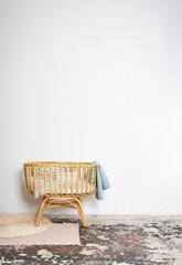 Babybett aus Bambus vor weißer Wand