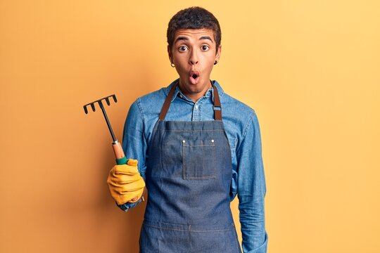 Young african amercian man wearing gardener apron and gloves holding rake scared and amazed with open mouth for surprise, disbelief face
