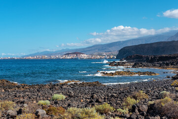 Volcanic rocky landscape of Malpais de la Rasca, a natural reserve close to Palm-Mar town, with views towards Atlantic Ocean and the tourist resort Los Cristianos, in Tenerife, Canary Islands, Spain