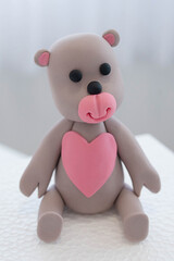 Teddy bear with pink heart cake topper, cute edible decoration made out of colorful sugar paste or fondant icing ready to place on a cake, usual dessert for baby showers, birthdays or special occasion