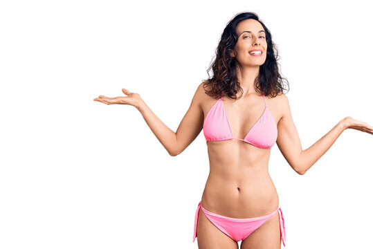 Young beautiful hispanic woman wearing bikini smiling showing both hands open palms, presenting and advertising comparison and balance