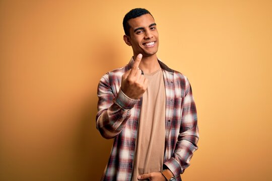 Young handsome african american man wearing casual shirt standing over yellow background Beckoning come here gesture with hand inviting welcoming happy and smiling
