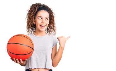 Beautiful kid girl with curly hair holding basketball ball pointing thumb up to the side smiling happy with open mouth