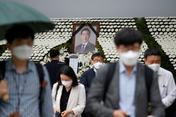 People react as they walk by a memorial altar for late Seoul Mayor Park Won-soon at Seoul City Hall Plaza in Seoul