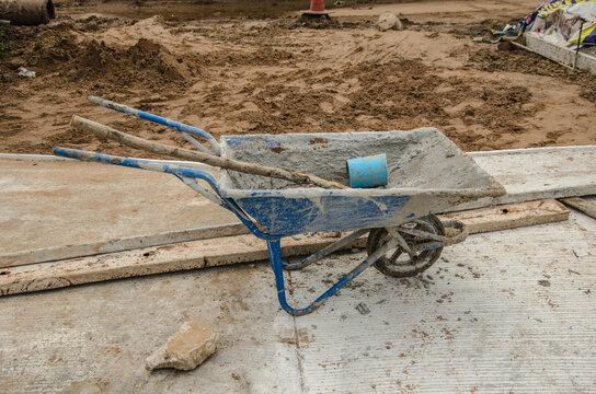 Dirty blue wheelbarrow on concrete floor