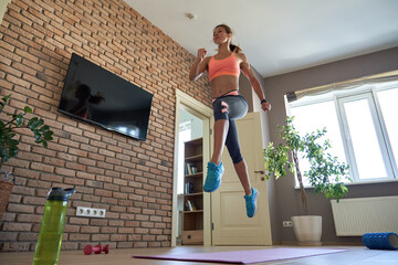 Fit sporty active young adult woman wearing sportswear doing fitness sport exercise at home....