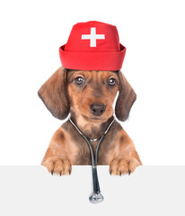 Poster Montagne Dachshund puppy dressed like a doctor with medical hat and stethoscope looks above white banner. isolated on white background. Empty space for text