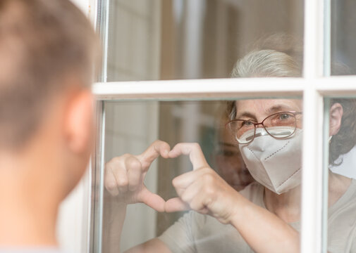 Grandmother wearing protective mask communicates with her grandson through a window during an epidemic of coronavirus and shows heart sign