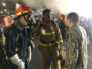 Sailors aboard the U.S. Navy amphibious assault ship USS Bonhomme Richard discuss a fire aboard the ship at Naval Station San Diego
