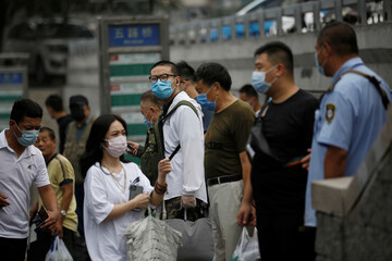 People wearing face masks wait at a bus stop during morning rush hour, following the outbreak of the coronavirus disease (COVID-19), in Beijing