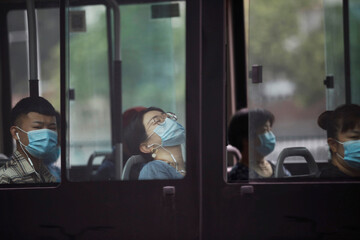 People wearing face masks sit on a bus during morning rush hour, following the outbreak of the coronavirus disease (COVID-19), in Beijing