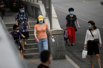 People wearing face masks walk on a street, following the outbreak of the coronavirus disease (COVID-19), in Beijing