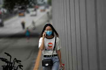 Woman wearing a face mask uses her phone as she walks on a street, following the outbreak of the coronavirus disease (COVID-19), in Beijing