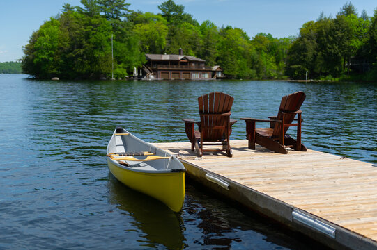 Two Adirondack chairs on a wooden dock facing a calm lake in Muskoka, Ontario Canada. A yellow canoe is tied to the dock. A cottage nestled between trees is visible across the water.